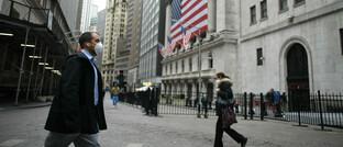 Passanten mit Schutzmasken in der Wall Street in New York: Nach massiven Kurseinbrüchen haben sich die Aktienmärkte wieder etwas erholt, sind aber von ihren Höchstständen weit entfernt.