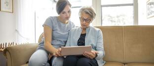Ein junge und eine ältere Frau sehen auf einen Laptop (Symbolbild): Unternehmenschefs sollten beizeiten ihre Nachfolge planen, rät FPSB-Deutschland-Chef Rolf Tilmes.