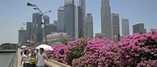 Flaneure auf der Esplanade mit der Skyline von Singapurs Geschäftsviertel im Hintergrund. Der Stadtstaat ist auch Sitz der Immobilienboutique Pamfleet, bei der Schroders die Mehrheitsbeteiligung erwerben wird.