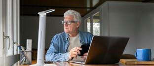 """Nachdenklicher Mann am Laptop. Die Allianz will mit dem digitalen """"Rentenkompass"""" für einen besseren Überblick bei der Altersvorsorge bieten"""