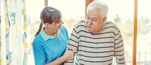 Pflegerin mit altem Mann. Oftmals müssen Kinder für ihre Eltern im Pflegeheim Unterhalt zahlen.