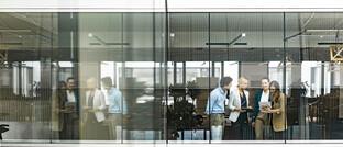 Eine Besprechung hinter den Glasfenstern eines Bürogebäudes: Büros bleiben für den Austausch und die persönlichen Kontakte relevant.
