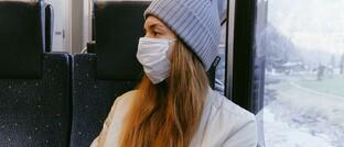 Frau mit Atemschutzmaske im Zug: Viele Menschen wollen von ihrer Krankenkasse wissen, was passiert, wenn ihre Corona-Warn-App Alarm schlägt.
