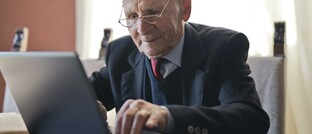 """Älterer Mann arbeitet am Laptop: """"Wer härter arbeitet, stirbt früher"""", erklärt der DGB."""