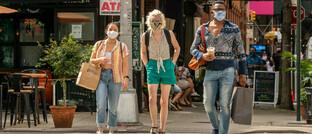 Shopping mit Maske in New York: In der US-Metropole, die im Februar und März stark von der Pandemie betroffen war, blieb die Zahl der Neuinfektionen zuletzt niedrig – viele Geschäfte und Kultureinrichtungen haben wieder geöffnet.
