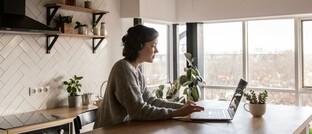 Frau arbeitet am heimischen Küchentisch: Arbeitnehmer sind im Homeoffice anders versichert als im Büro des Arbeitgebers.