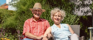 Senioren vor ihrem Eigenheim
