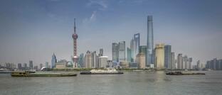 Frachtschiffe vor der Skyline von Shanghais Finanzviertel Pudong: Chinesische Banken stützen die Wirtschaft mit Krediten – und müssen Gewinneinbußen hinnehmen.
