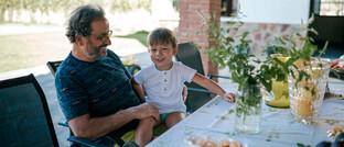 Rentner mit Enkelkind auf der Terrasse seines Ferienhauses