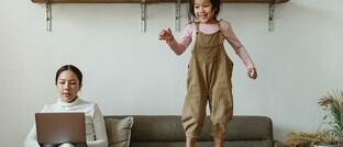 Frau versucht Home-Office und Kinderbetreuung zu vereinbaren