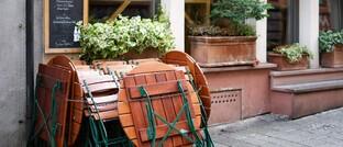 Zusammengeklappte Stühle und Tische vor einer Kneipe in der hessischen Landeshauptstadt Wiesbaden