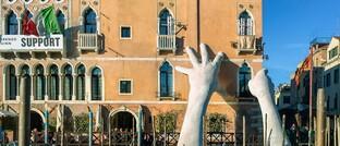 Hände-Skulptur stützt ein Haus am Canale Grande in Venedig
