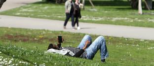 Mann mit Smartphone auf einer Wiese