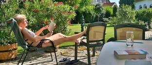Seniorin im Garten ihres Hauses in Apetlon, im österreichischen Burgenland