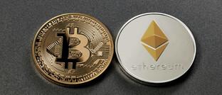 Symbolische Bitcoin- und Ether-Münzen