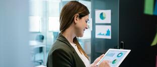 Frau schaut sich Finanzanalyse auf dem Tablet an