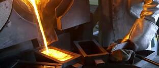 Arbeiter gießt flüssiges Gold