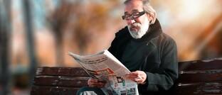 Älterer Mann liest Zeitung
