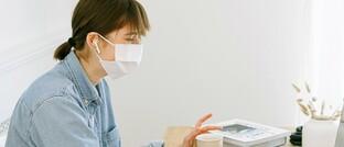 Frau arbeitet mit Mundschutz im Büro