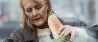 Seniorin packt ihren Lebensmitteleinkauf aus