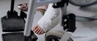 Frau mit Gips im Rollstuhl