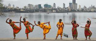 Schülergruppe übt sich in klassischem Tanz vor der Skyline von Mumbai