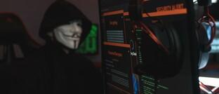 Mit Anonymous-Maske vorm Bildschirm