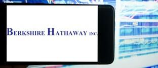 Das Logo von Berkshire Hathaway auf einem Handy neben einer Illustration des Aktienmarkts