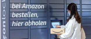 Eine Frau holt gerade ihre Pakete an einem Amazon-Locker im Franken-Center in Nürnberg ab. Die Corona-Pandemie treibt das Geschäft von Amazon weiterhin enorm an.