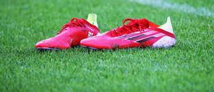 Sportschuhe von Adidas auf Fußballrasen