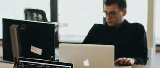 Mann am PC und Laptop im Büro