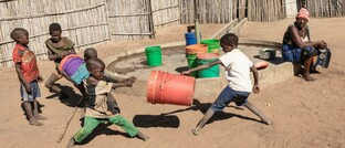 Kinder an einem Dorfbrunnen in Mosambik