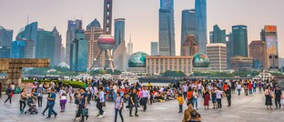 Touristen tummeln sich auf einem Platz mit Blick auf die Skyline von Shanghai